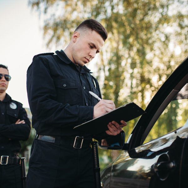 Male police officers in uniform check vehicle on the road. Law protection, car traffic inspector, safety control job